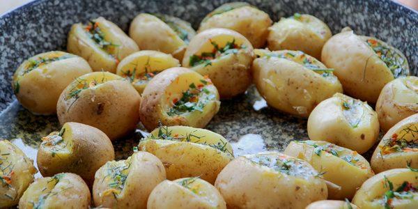 Verse, nieuwe aardappelen met zelfgemaakte kruiden- en bloemenboter